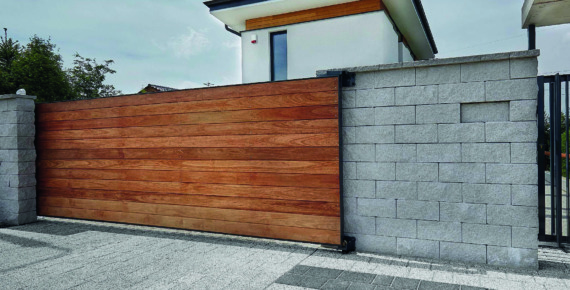 Drewniana brama przesuwna w ogrodzeniu domu
