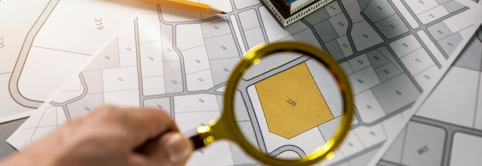 mężczyna sprawdza lupą działkę na mapie