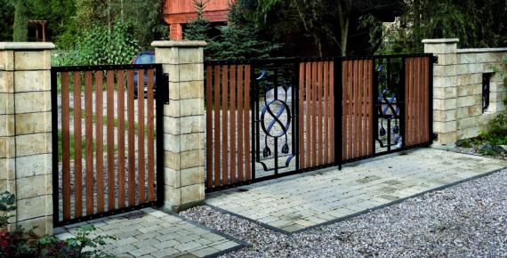 Drewniane ogrodzenie z czarnymi metalowymi okuciami i kamiennymi słupkami