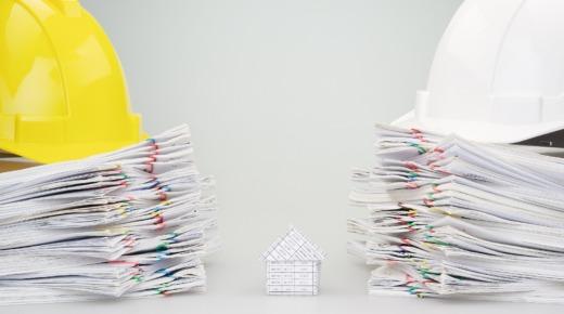 Mały dom z papieru pomiędzy stosem dokumentów na których leżą kaski