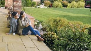 kobieta i mężczyzna siedzą na podłodze tarasu i patrzą na ogród