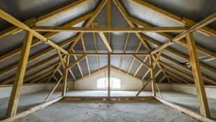 poddasze budynku z drewnianymi belkami i małym oknem