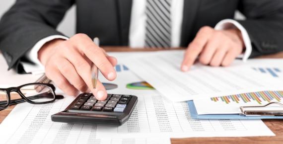 Mężczyzna w garniturze liczy na kalkulatorze