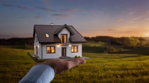 model domu na dłoni nad działką budowlaną