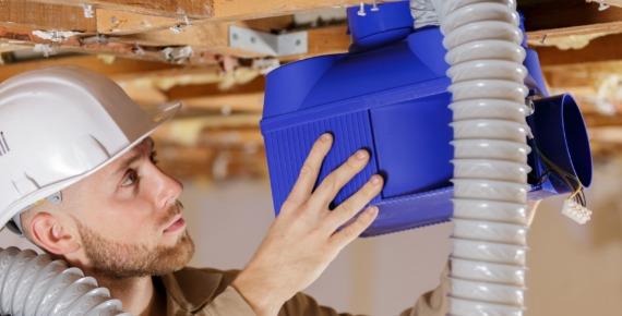 mężczyzna zakłada wentylację mechaniczną w budynku